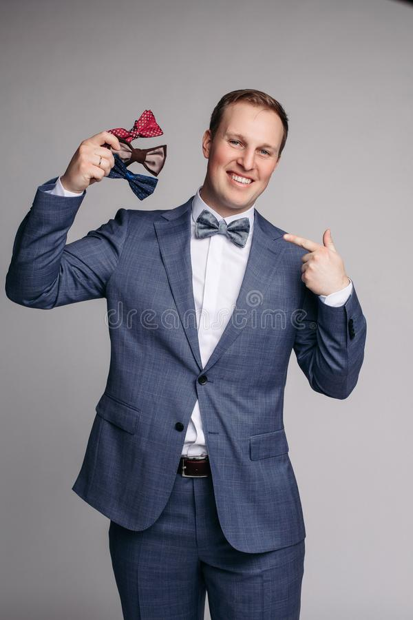 Smiling man insmart suit keeping bow ties in hand royalty free stock image