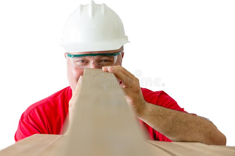 Smiling man inspecting quality of wooden plank royalty free stock photos