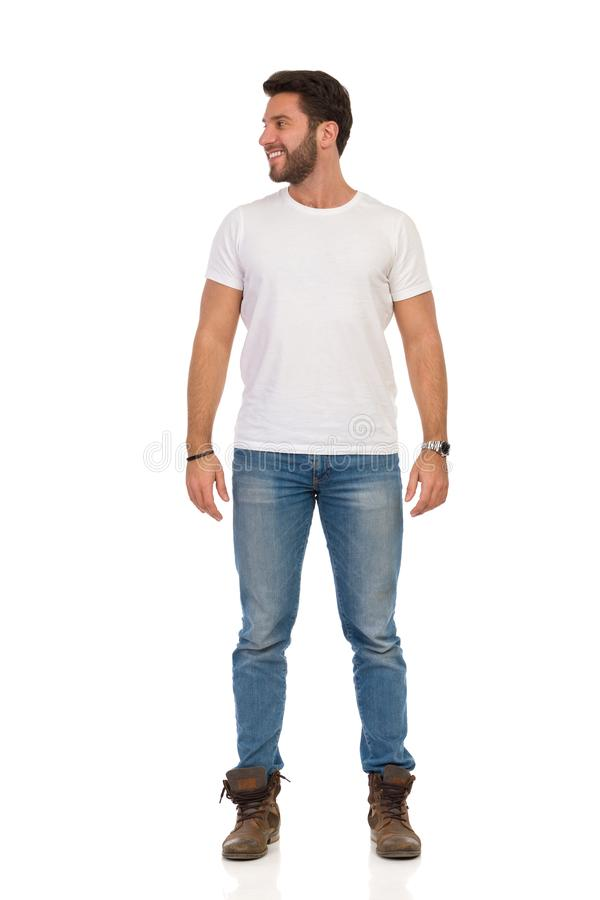 Smiling Man In Jeans And White T-shirt Is Standing And Looking Away. Front View. Full length studio shot isolated on white stock image