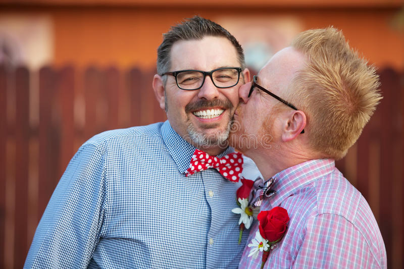 Smiling Man Kissed By Spouse. Smiling men with eyeglasses being kissed by spouse royalty free stock image