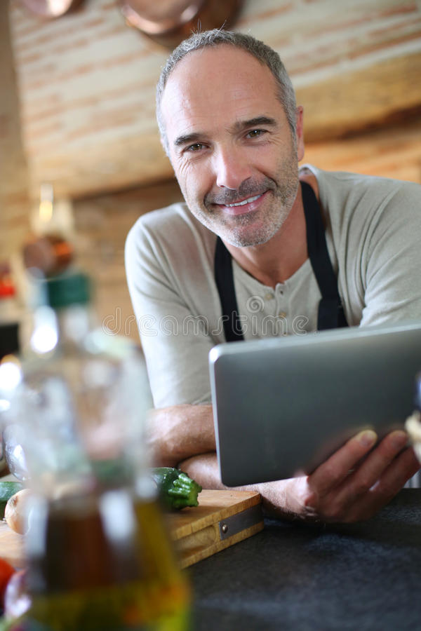 Smiling man in kitchen checking recipe on internet stock photography