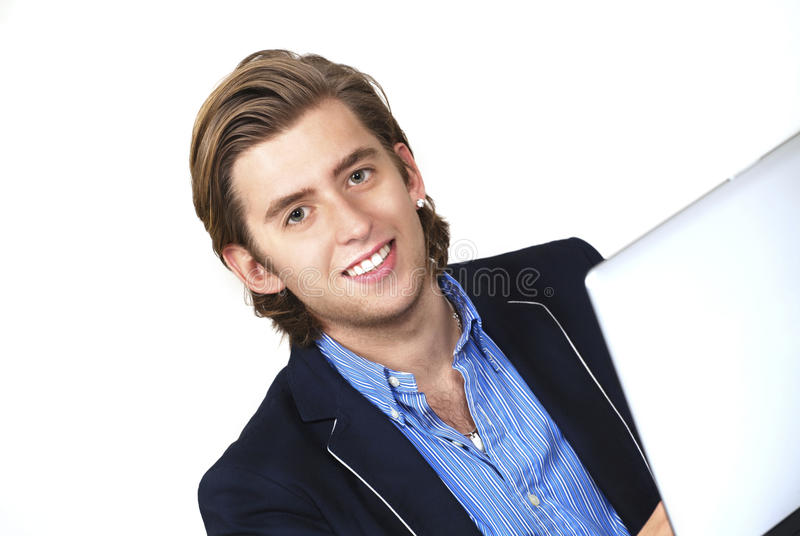 Smiling man on laptop. Handsome smiling young man working on laptop stock photo