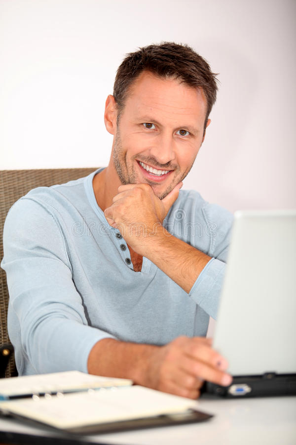 Smiling man with laptop computer stock photography
