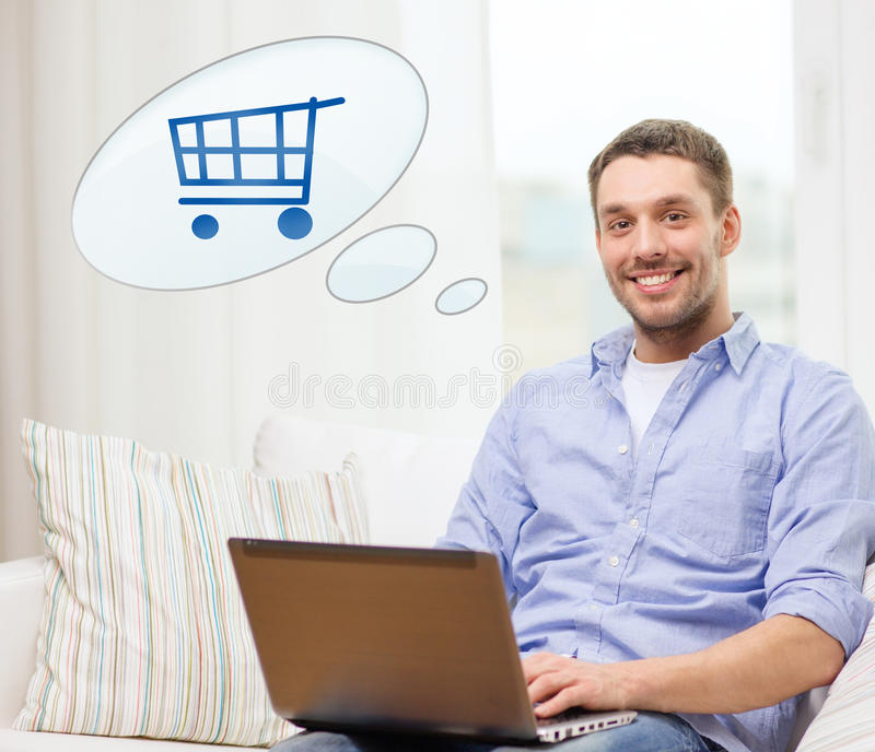 Smiling man with laptop shopping online at home. People, leisure and technology concept - smiling young man with laptop computer and trolley icon shopping online stock photography