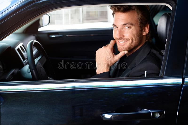 Smiling man in limousine. Smiling handsome man sitting in limousine stock photography