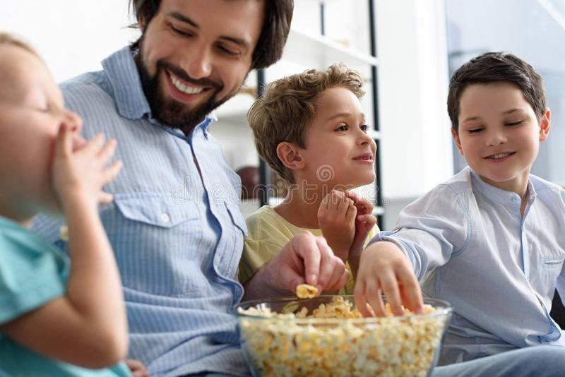 smiling man and little sons eating popcorn while watching film together royalty free stock photos