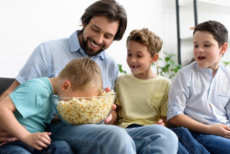 smiling man and little sons eating popcorn while watching film together royalty free stock image