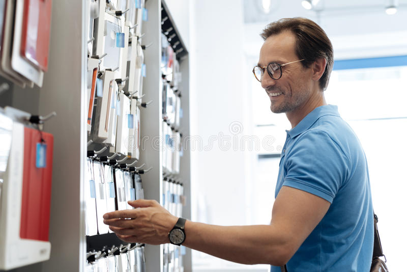 Smiling man looking at phone covers at store stock photography