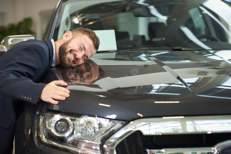 Smiling man lying on car hood and hugging auto. Front view of dark blue car, headlight and man lying on car hood and hugging auto. Happy owner of new automobile stock photos