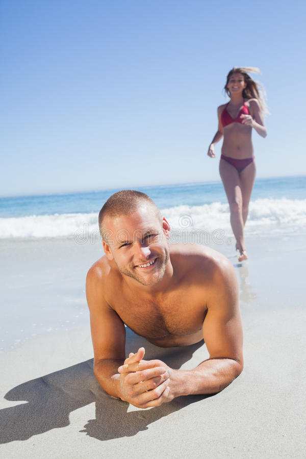 Download Smiling Man Lying On The Sand While Woman Running To Him Stock Image - Image: 33126273