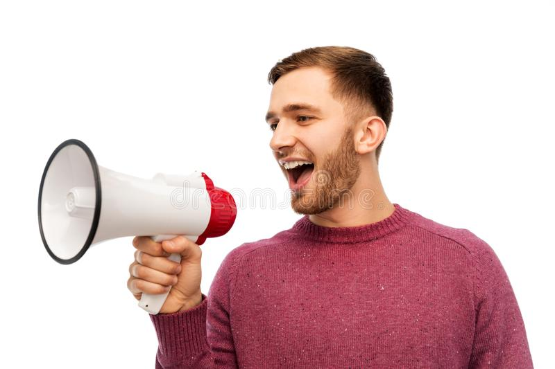Smiling man with megaphone. Communication and people concept - smiling young man with megaphone royalty free stock photos