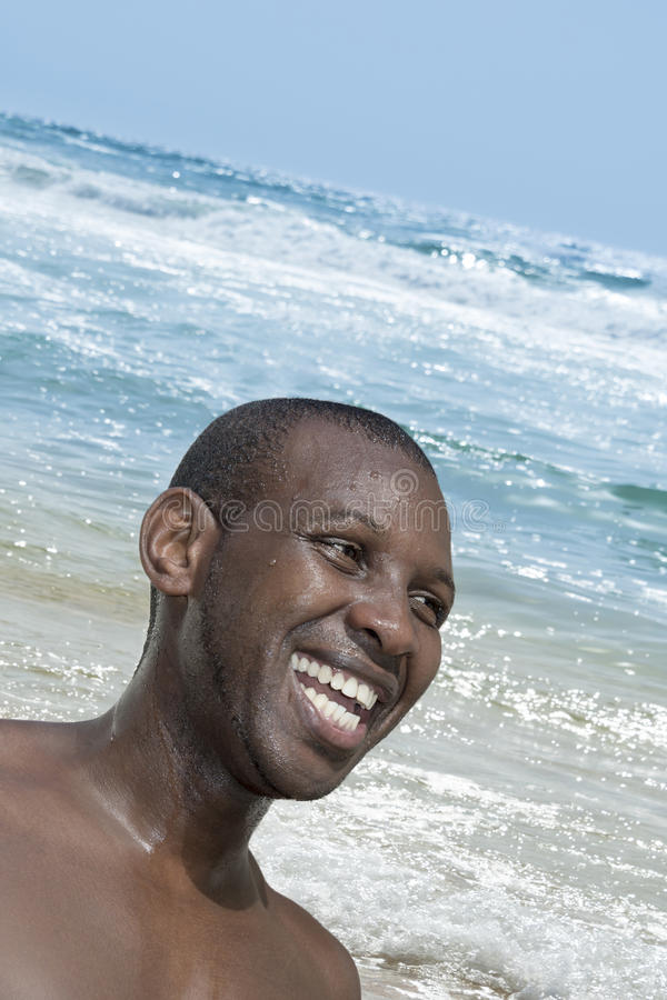 Smiling man near the raging Atlantic Ocean, Malika beach, Senegal stock photography