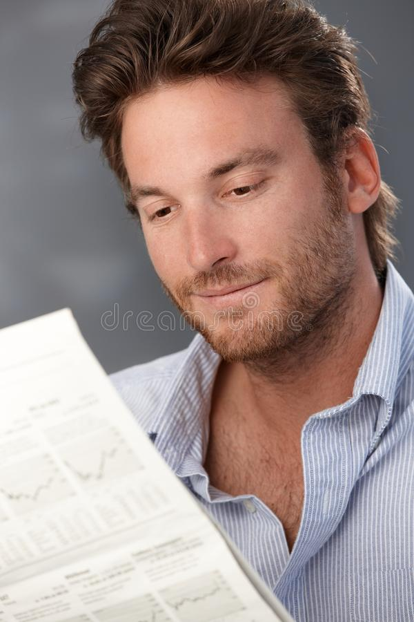 Smiling man with newspaper. Portrait of goodlooking smiling man reading newspaper stock photo