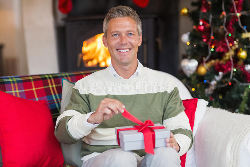 Smiling man opening a gift on christmas day. At home in the living room stock images