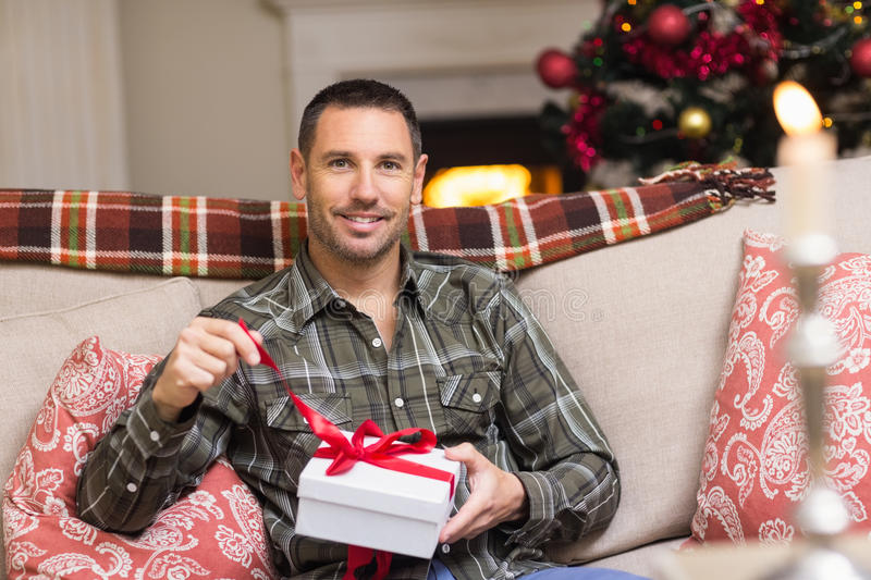 Smiling man opening a gift on christmas day. At home in the living room royalty free stock photography
