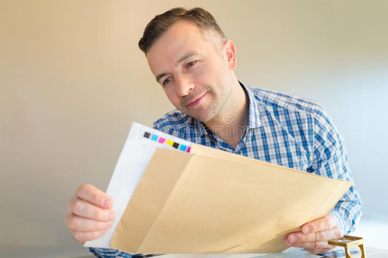 Smiling man opening letter with printing stock image