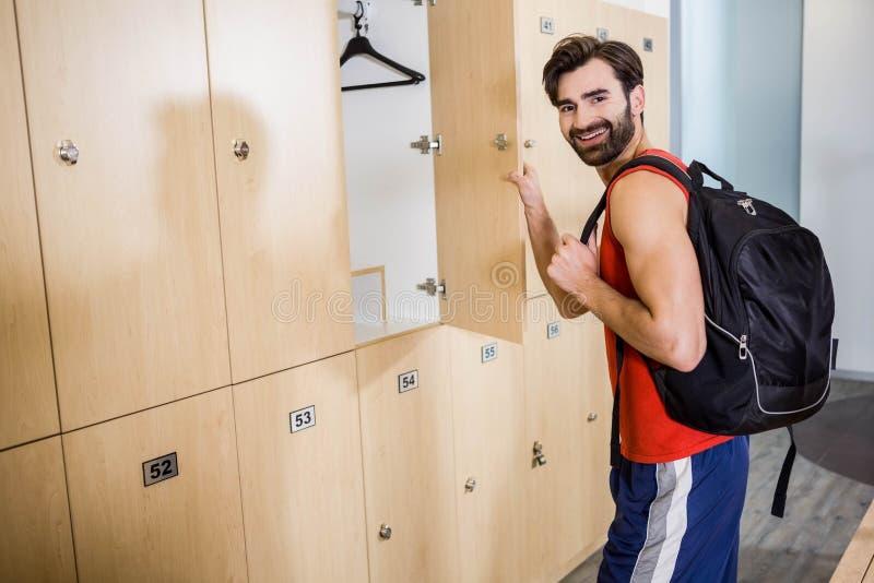 Smiling man opening locker stock photo