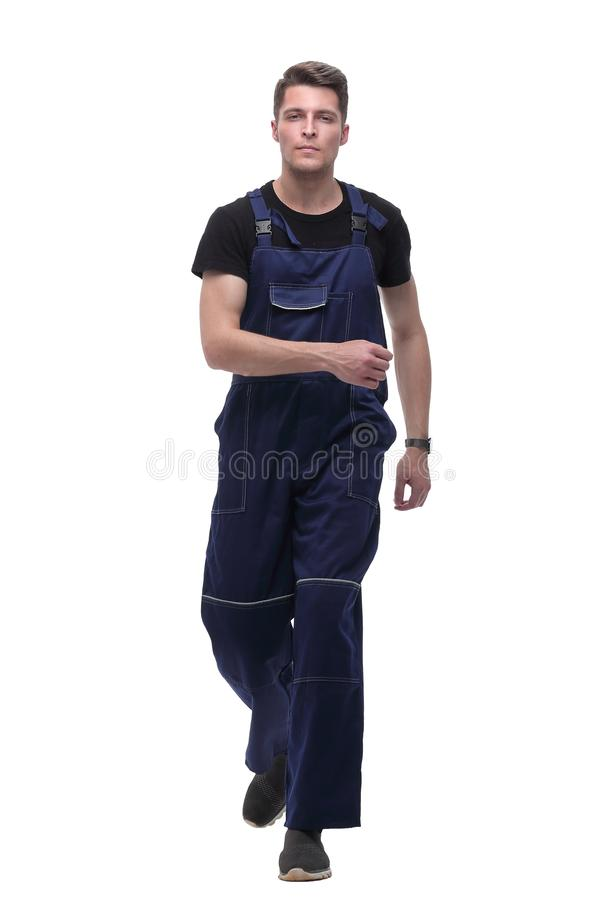 Smiling man in overalls goes forward.isolated on white stock photos