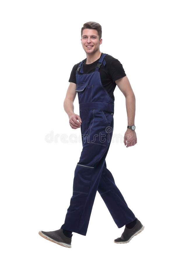 Smiling man in overalls goes forward.isolated on white royalty free stock photos