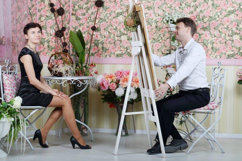 Smiling man paints portrait of woman. Smiling men paints portrait of women in beautiful retro interior stock photography