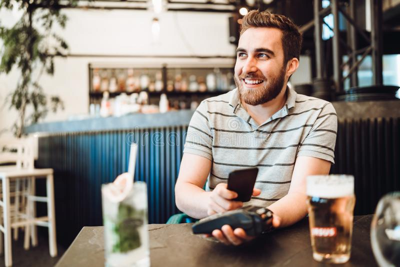 Smiling handsome man paying at restaurant using mobile pay technology, nfc modern payment system royalty free stock photography