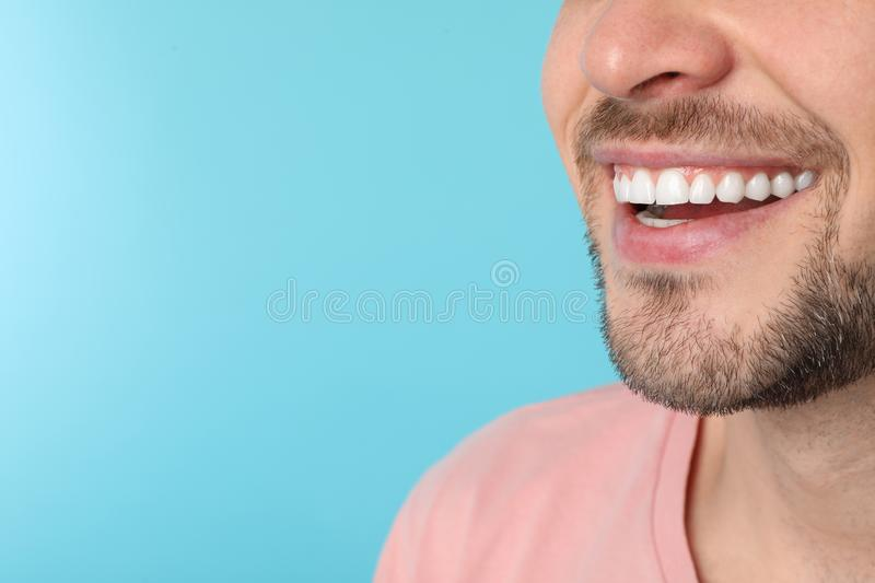 Smiling man with perfect teeth on color background, closeup. Space for text royalty free stock photography