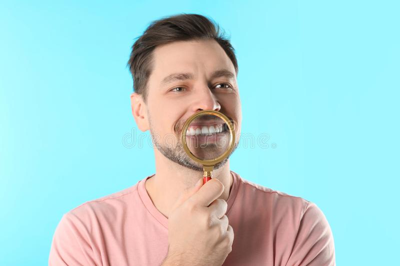 Smiling man with perfect teeth and magnifier. On color background royalty free stock photos