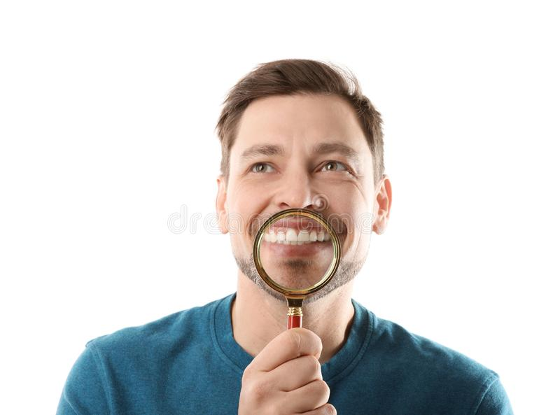 Smiling man with perfect teeth and magnifier. On white background stock photography