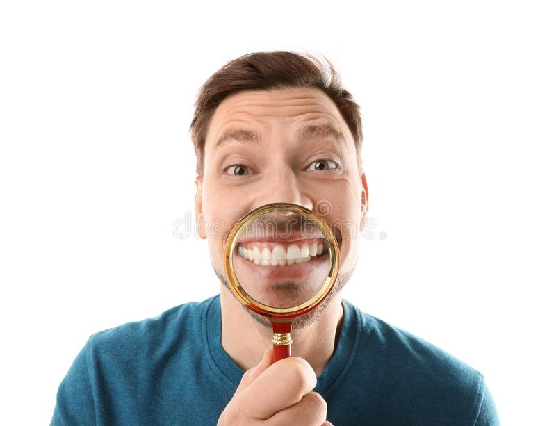 Smiling man with perfect teeth and magnifier. On white background stock photo
