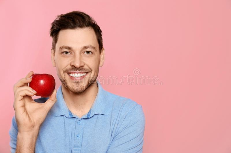 Smiling man with perfect teeth and red apple on color background. Space for text royalty free stock photos