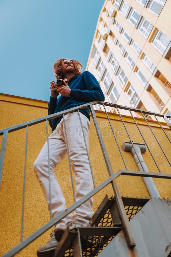 Smiling man with photo camera on stairs. Urban lifestyle concept. Full length low view portrait of young smiling red haired hipster guy with photo camera staying stock images