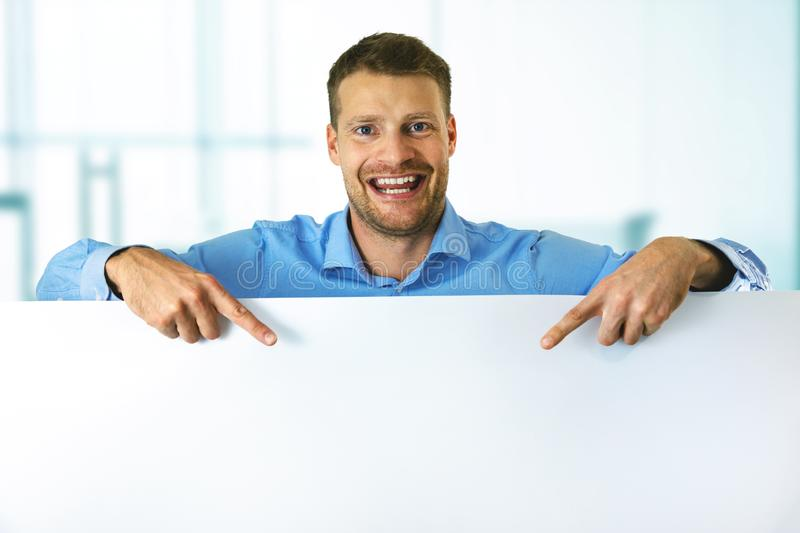 Smiling man pointing on white blank board with copy space royalty free stock image