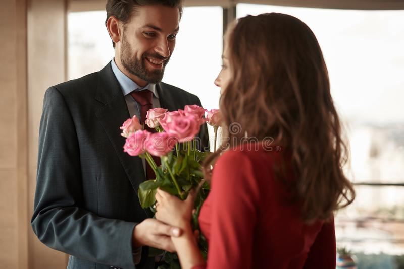 Smiling man presenting woman bunch of flowers. Concept of romantic engagement. Waist up portrait of cheerful gentleman tenderly holding hand of his lover with royalty free stock photo