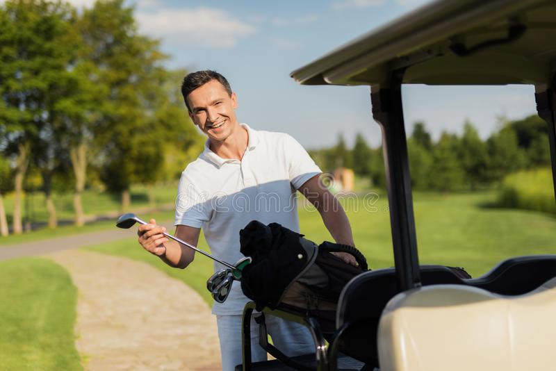 A smiling man pulls out of a bag with sticks, a golf club. Bag lies on the luggage compartment of the golf cart stock image