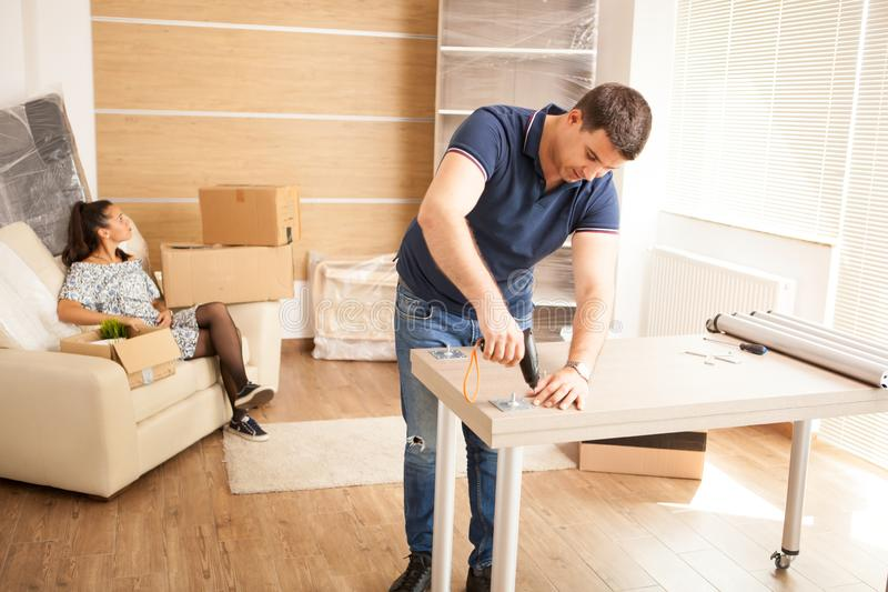 Smiling man putting together self assembly furniture in new home. Smiling men putting together self assembly furniture in new home. Furniture in new house royalty free stock images