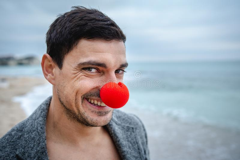 Smiling man with a red nose on the beach in morning hangover. Smiling man with a red clown nose partying lonely on the beach. Christmas holiday party royalty free stock image