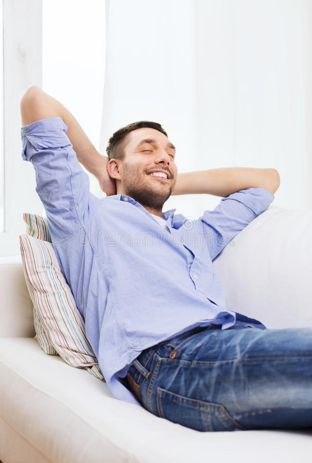 Smiling man relaxing on couch at home royalty free stock image