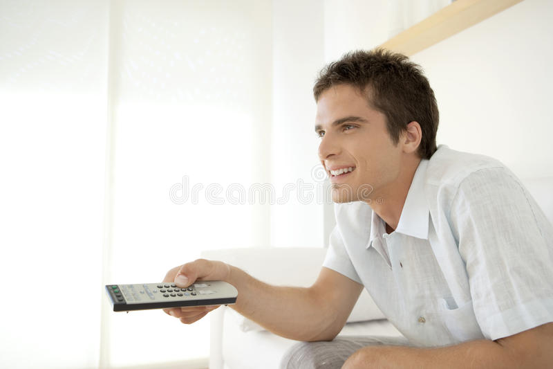 Smiling Man with Remote Control stock photography