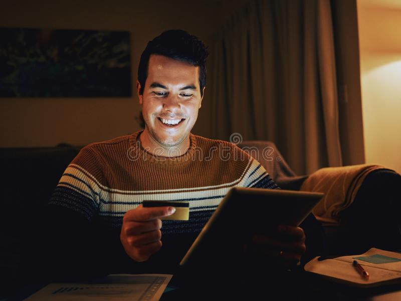 Smiling man shopping online late at night using credit card and. Portrait of a happy man in the living room looking at credit card and digital tablet shopping stock photography