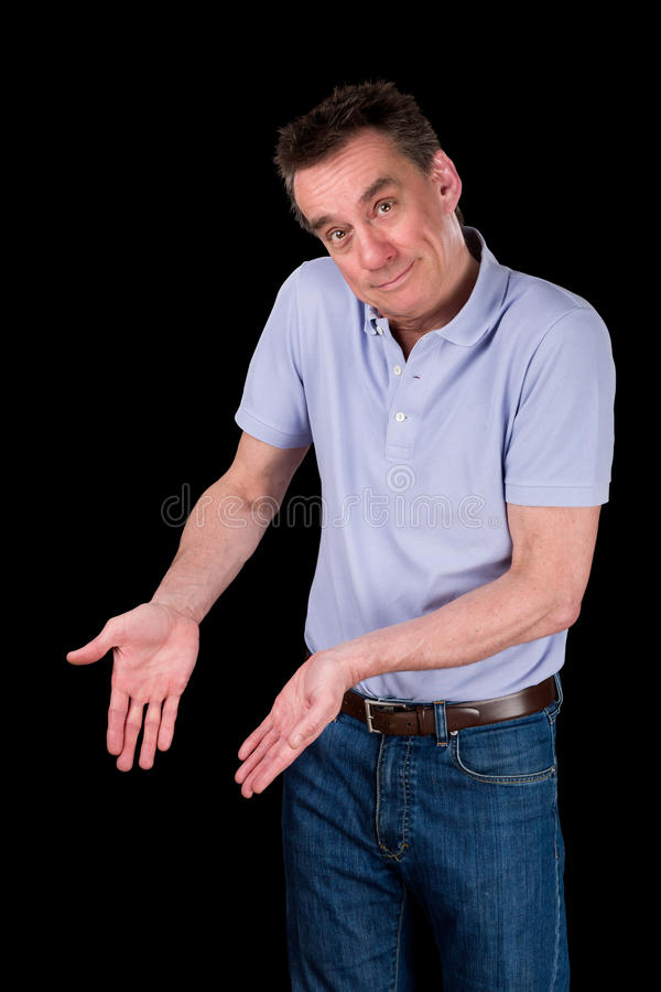 Smiling Man Shrugging Hands Forward Pointing. Smiling Middle Age Man Shrugging Hands Forward Pointing at Something Black Background royalty free stock photos