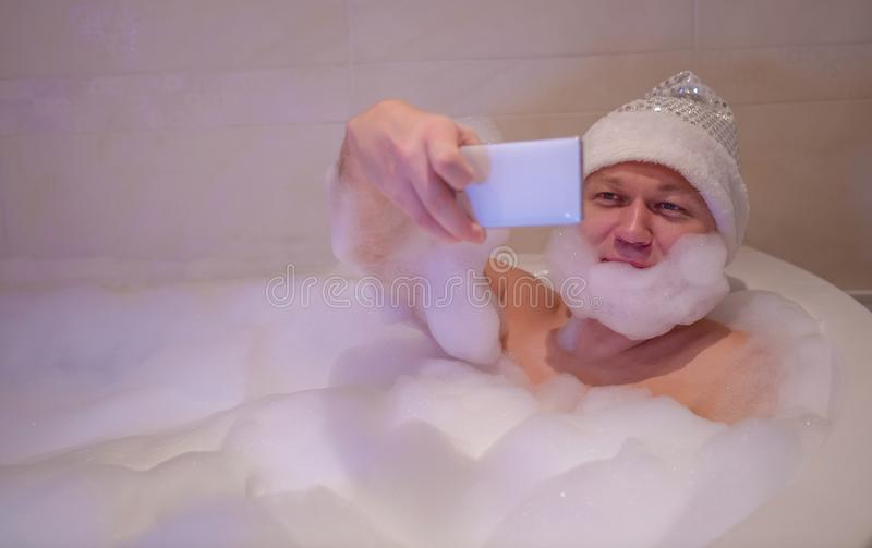 Young smiling man sits in the bathroom, makes a beard of foam and takes a selfie royalty free stock photography