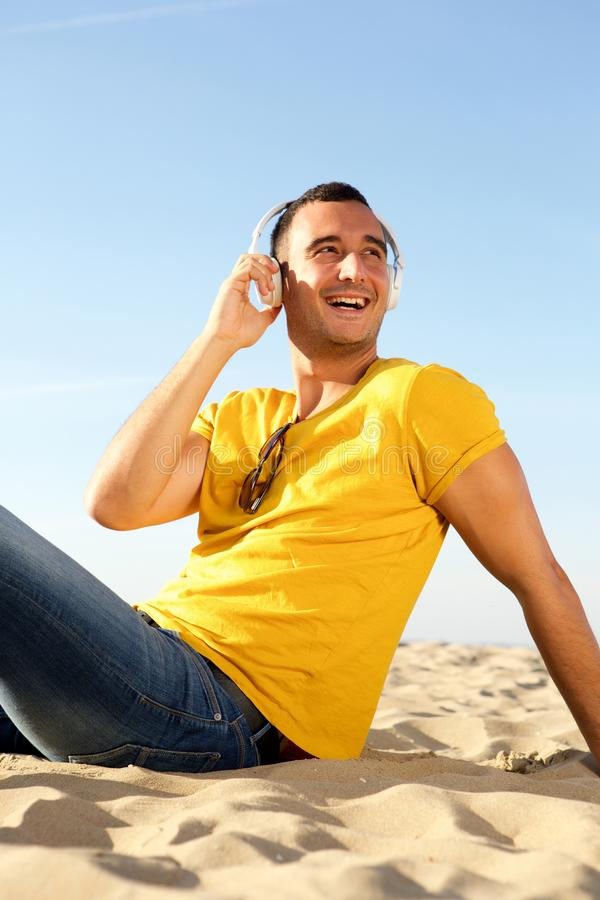 Smiling man sitting on beach listening to music. Portrait of smiling man sitting on beach listening to music stock photos