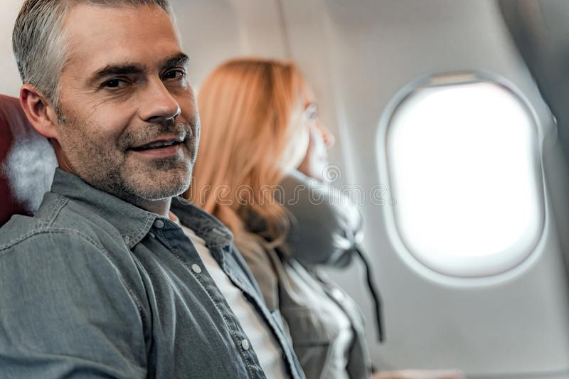 Smiling man sitting near woman in cabin stock image