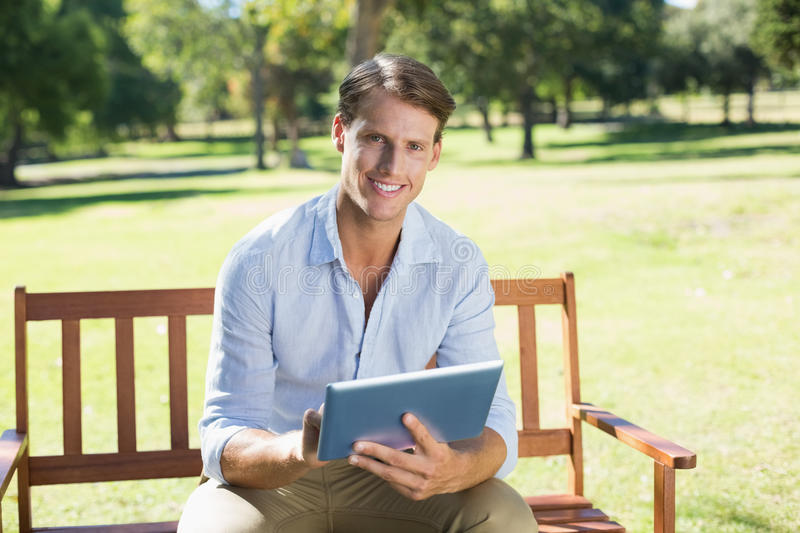 Smiling man sitting on park bench using tablet looking at camera stock images