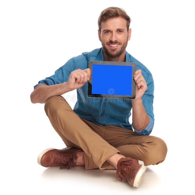 Smiling man sitting and showing the blank screen on tablet. Smiling casual man sitting and showing the blank screen on tablet on white background royalty free stock photography