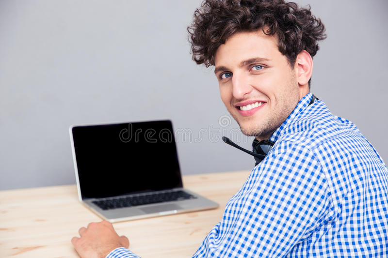 Smiling man sitting at the table with laptop. Portrait of a smiling man sitting at the table with laptop and looking back at camera royalty free stock photos