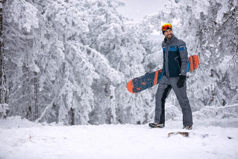 Smiling man with ski mask holding his snowboard, extreme sport a royalty free stock photo