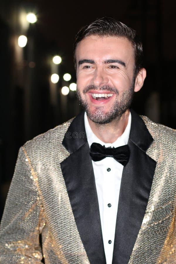 Smiling man in sparkly golden tuxedo smiling. - Stock image stock photo