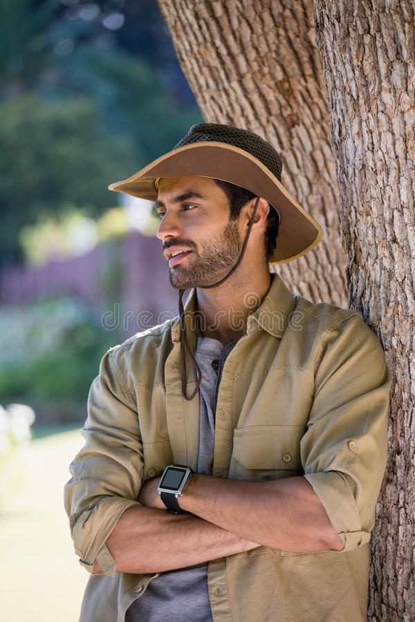 Smiling man standing with arms crossed near tree trunk stock photo
