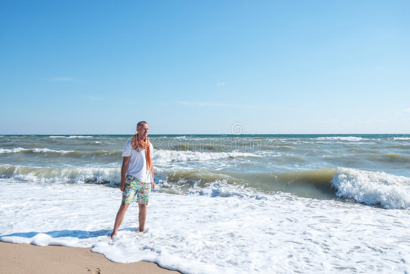 Smiling man standing on the beach. At the sunny windy day stock photography